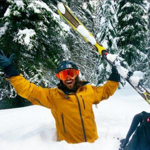 Skiier waist deep in snow.